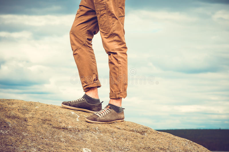 Feet man standing on rocky mountain outdoor. Travel Lifestyle vacations concept with sky clouds on background retro colors stock photo