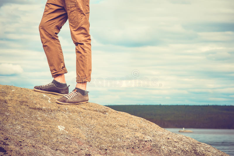 Feet man standing on rocky mountain outdoor. Travel Lifestyle vacations concept with sky clouds on background retro colors royalty free stock photo