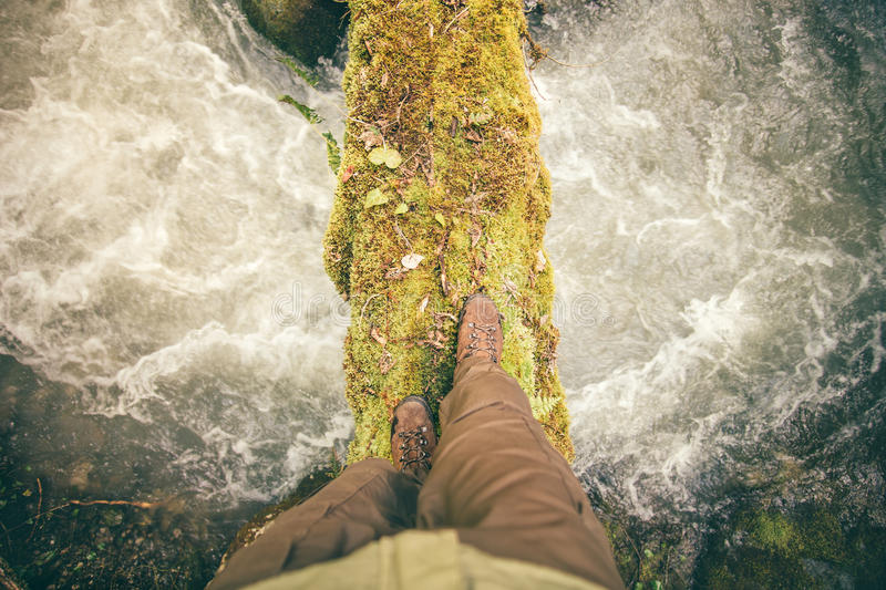Feet Man trekking boots hiking outdoor Lifestyle. Travel survival concept with river and stones on background top view royalty free stock photos