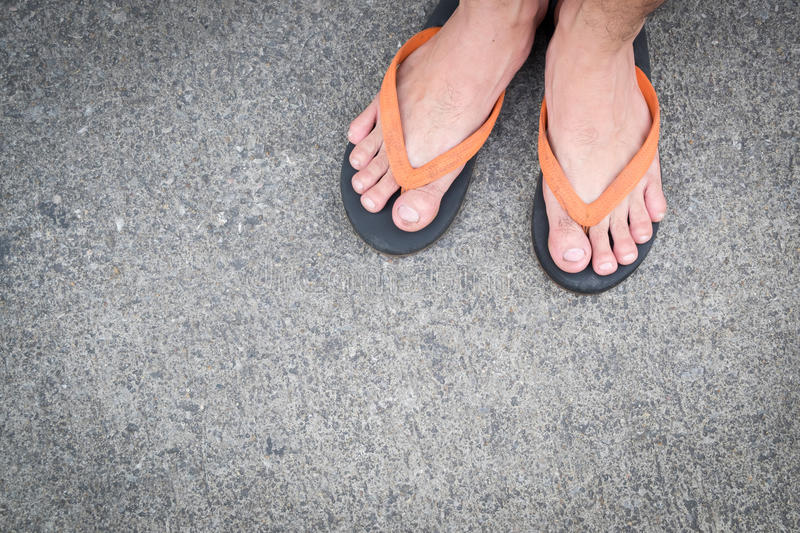 Feet of a man wearing sandals on concrete floor. Feet of a man wearing sandals on the old concrete floor royalty free stock photography