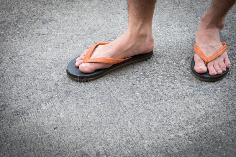 Feet of a man wearing sandals on concrete floor. Feet of a man wearing sandals on the old concrete floor stock photos