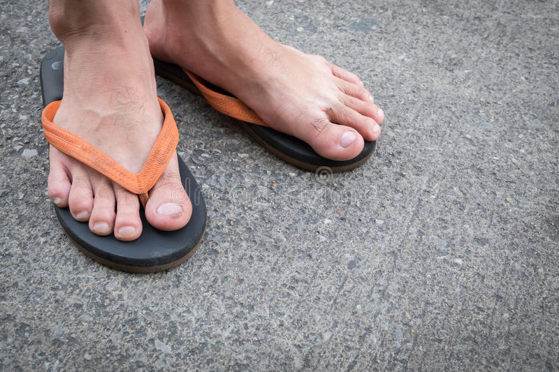 Feet of a man wearing sandals on concrete floor. Feet of a man wearing sandals on the old concrete floor stock photo
