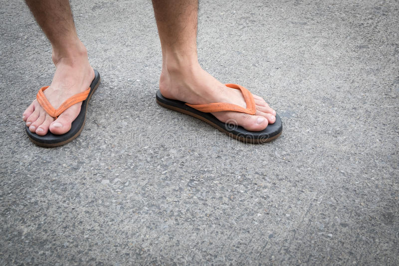 Feet of a man wearing sandals on concrete floor. Feet of a man wearing sandals on the old concrete floor royalty free stock photo