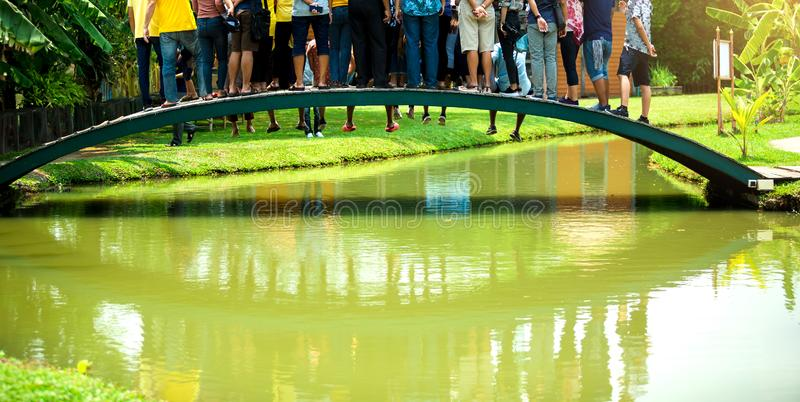 Feet of many people sit and stand to take pictures on the curved wooden bridge stock photo