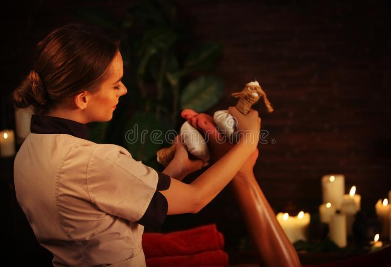Feet massage with Thai reflexology. Cropped shot of foot reflexology. Body part of female hand and leg on candels background. Masseuse in foreground. Rest in royalty free stock images