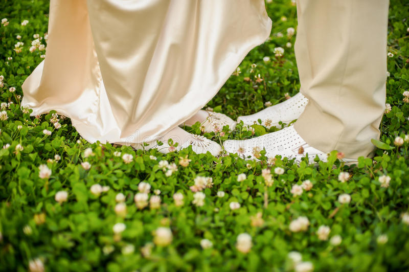 The feet of men and women in white on clover royalty free stock photos