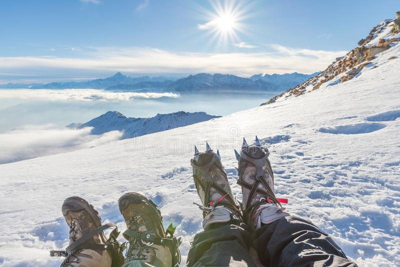Feet on mountain top in backlight. Hiking boot with crampons for ice and snow climbing. Feet on mountain top in backlight. Hiking boot with crampons for ice and royalty free stock photography