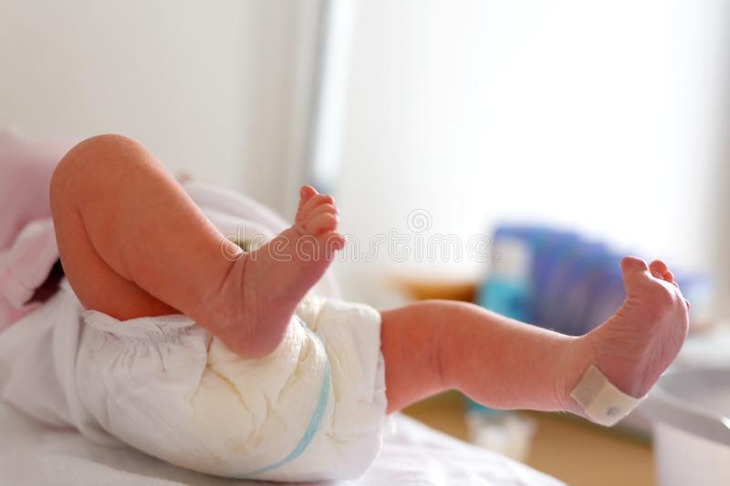 Feet of Newborn baby child seconds and minutes after birth lying on towel royalty free stock photo