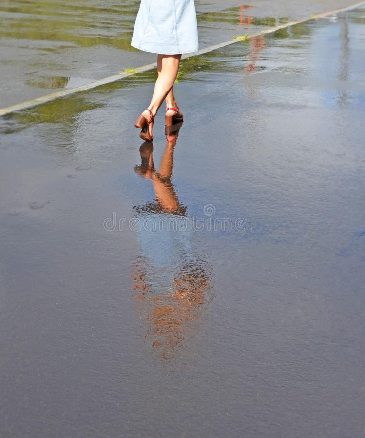 Free Feet Of The Girl And Her Reflection In Water On The Sidewalk Royalty Free Stock Image - 126213446