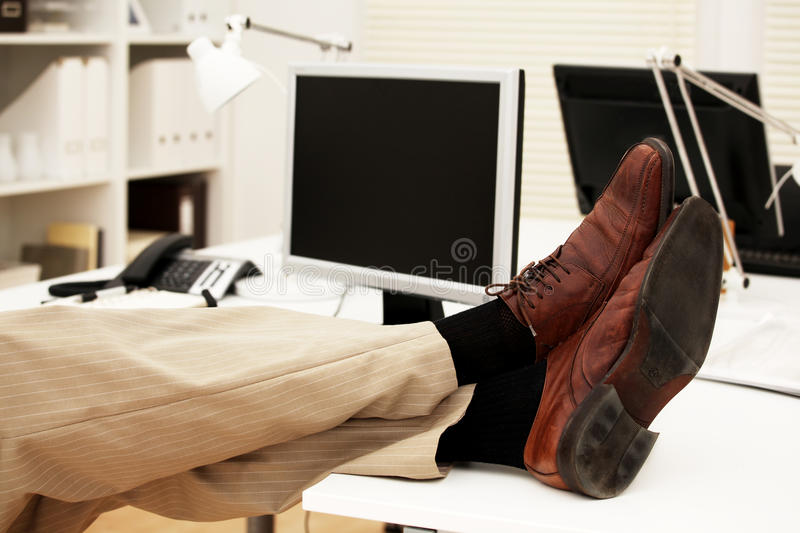 Feet on the office desk royalty free stock photography