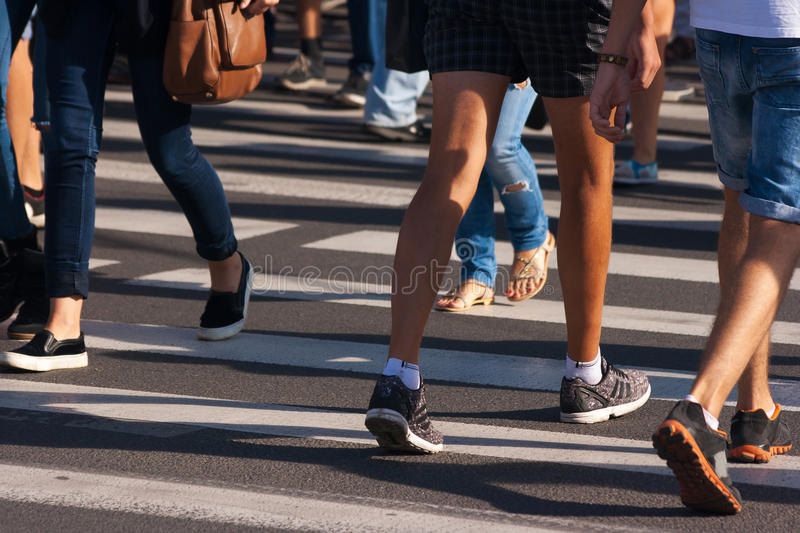 Feet of pedestrians. Walking on the crosswalk on city road royalty free stock photo