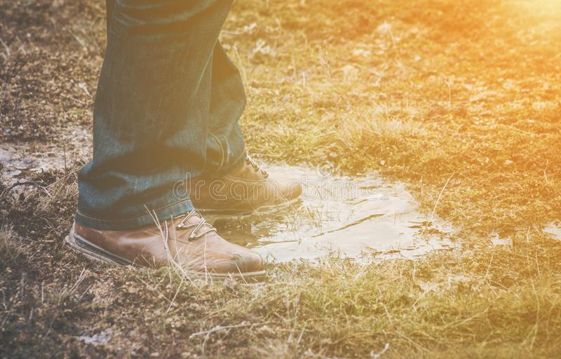 Feet of a person standing in a puddle of water. Feet of a person wearing lace up shoes and blue denim jeans standing in a puddle of water in short scrubby grass stock photos