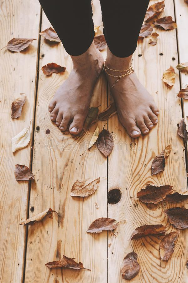 The feet of the person on the wooden floor covered with fall leaves. Autumn season concept with copy space stock photo