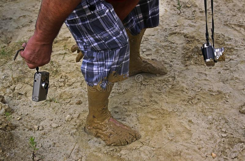 The feet of the photographer. In wet clay stock image