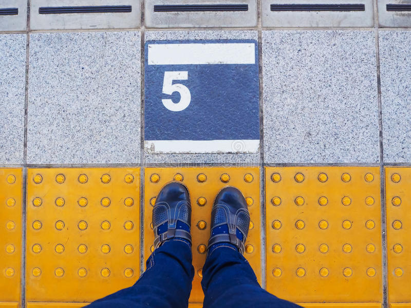 Feet on the platform number 5 at train station stock photo