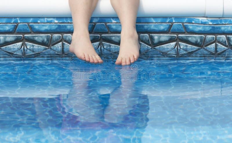 Feet in pool water stock photos