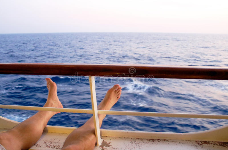 Feet relaxing by balcony of caribbean cruise ship. Spending holiday relaxing at caribbean cruise ship with view of horizon and sea stock photography