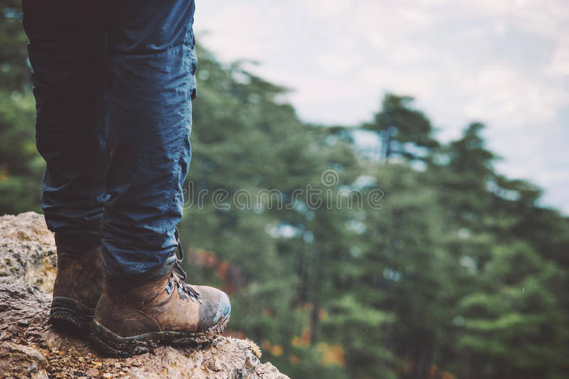 Feet on rocky cliff edge with forest aerial view. Travel Fashion Lifestyle adventure vacations concept trekking boots royalty free stock image