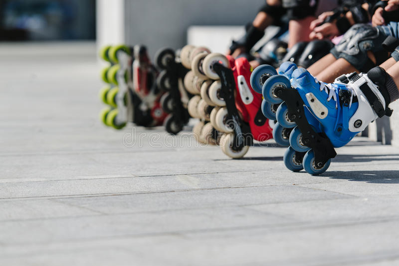 Feet of rollerbladers wearing inline roller skates sitting in outdoor skate park, Close up view of wheels befor skating. Feet of rollerbladers wearing inline stock images