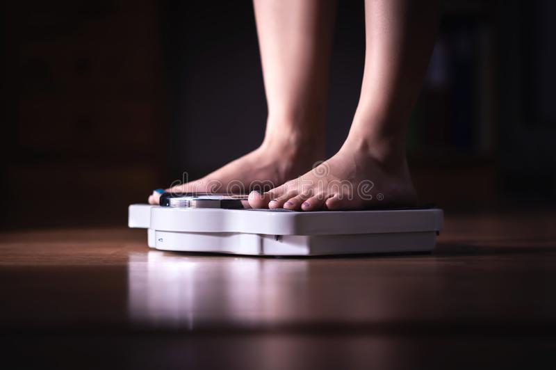 Feet on scale. Weight loss and diet concept. Woman weighing herself. Fitness lady dieting. Weightloss and dietetics. Dark late night mood royalty free stock photo