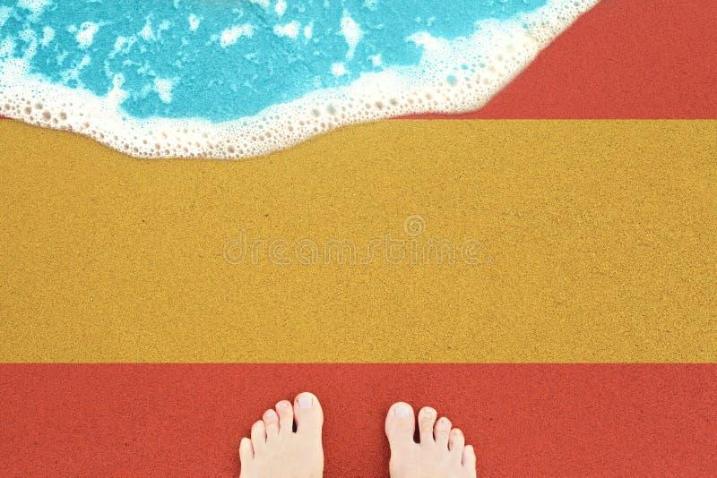 Feet on sea sand and surf. Vacation on ocean beach, summer holiday with flag Spain stock photography