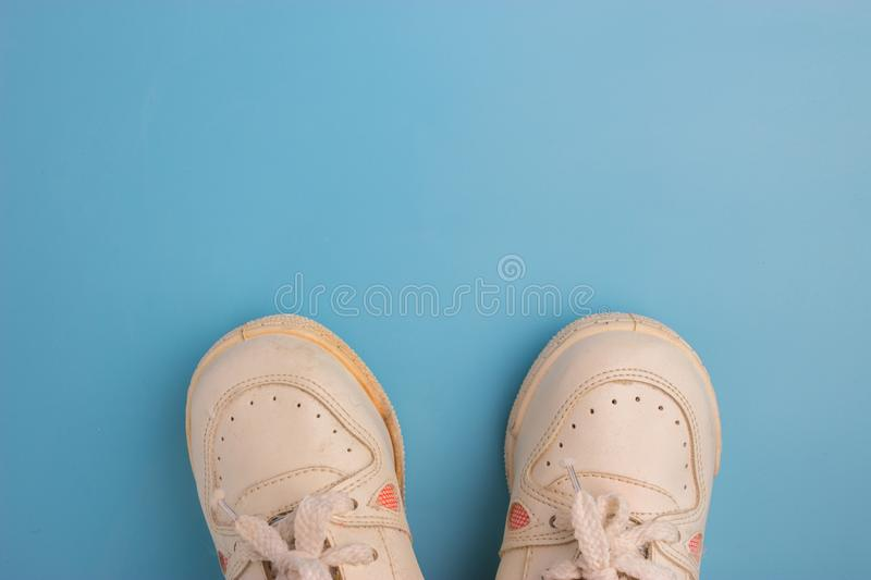 Feet selfie, fashion white sneakers. On blue background stock photography