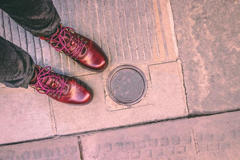 Fashionable burgundy boots on the city pavement and electric metallic bollard under ground. Retractable bollard royalty free stock image