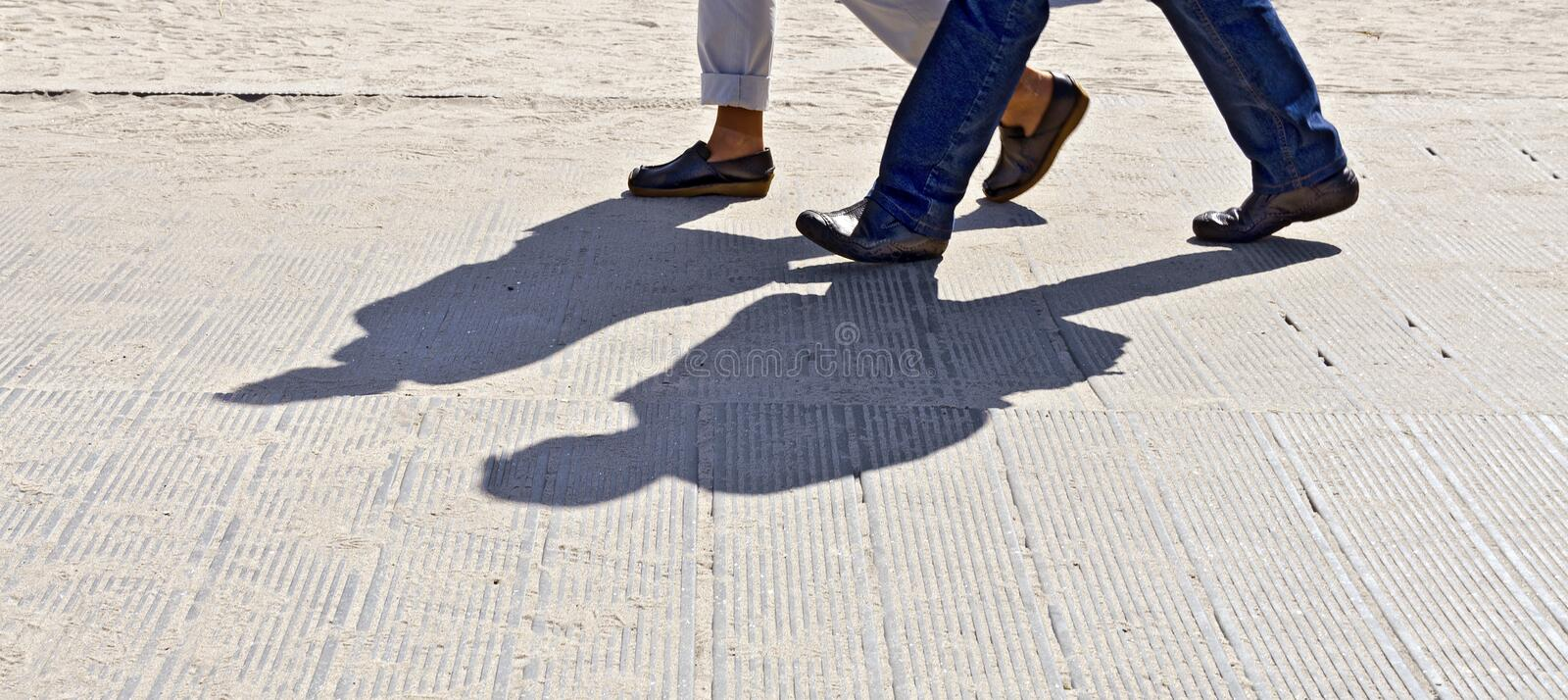 Feet and shadow of two walkers. On a sandy beach way, Zingst, Germany royalty free stock photography