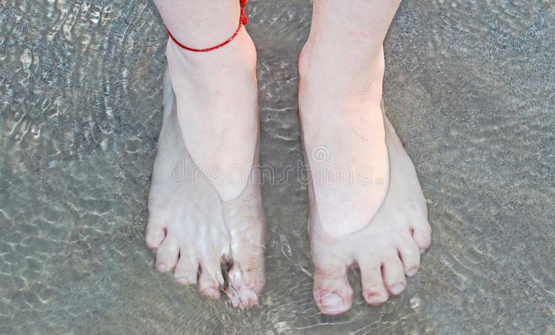 The feet in shallow water. The feet of a young woman wears a red bracelet for good luck in shallow water stock photos