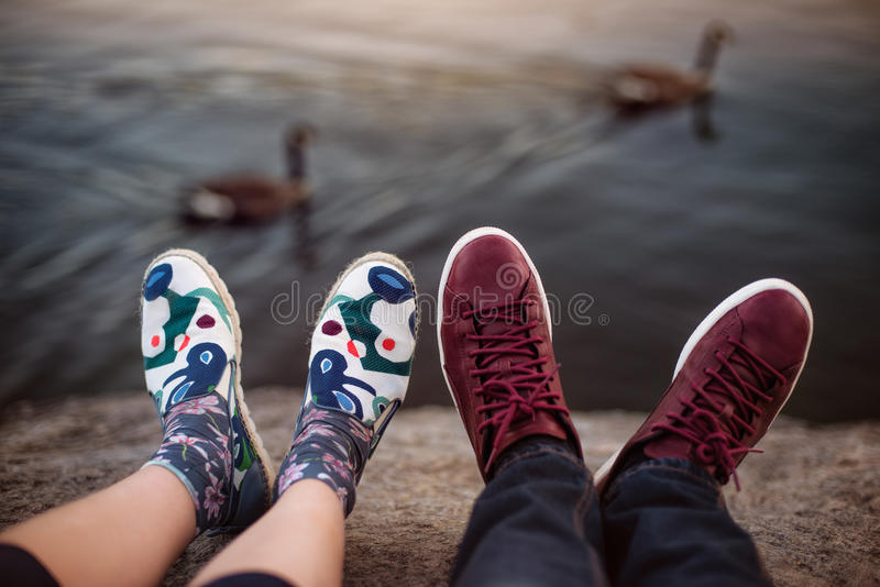 Feet with shoes of the couple on romantic date sitting on the rocks near lake.  royalty free stock photos