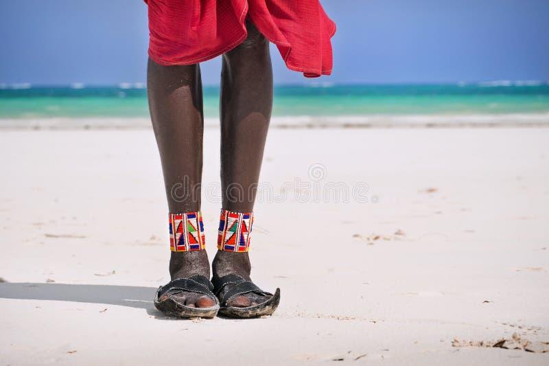 Feet and shoes Maasai. On the ocean beach royalty free stock photos
