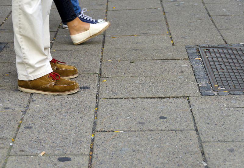 Feet of shoppers on a paved sidewalk. At a shopping street stock photos