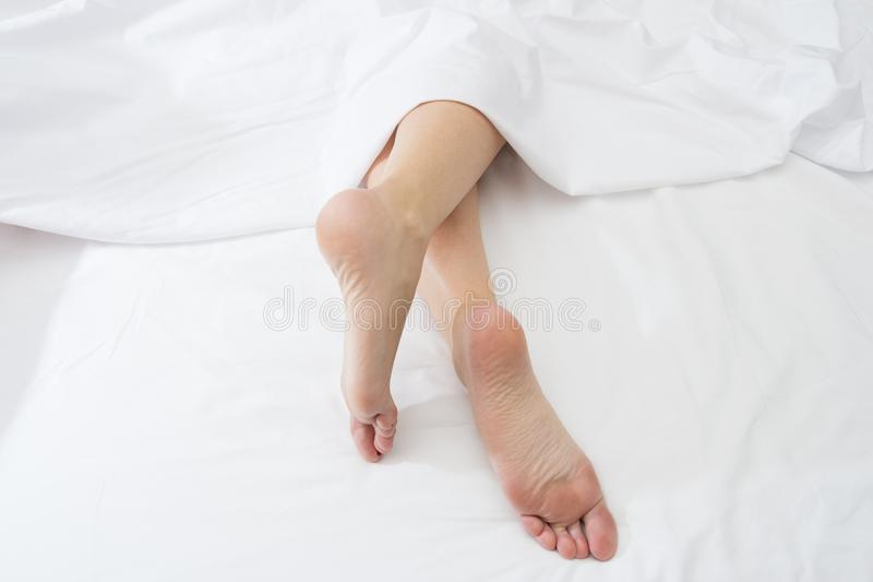 Feet of sleeping woman upside down on a white bed. stock photo