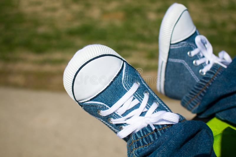 Feet with sneakers. Feet of a baby sneakers, selective focus royalty free stock photo