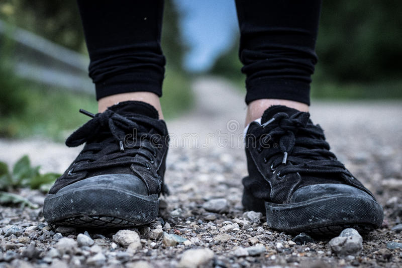 Feet with sneakers on rocks royalty free stock images