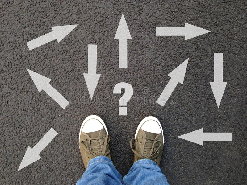 Feet standing on asphalt with multitude of arrows in diffrent directions stock photo