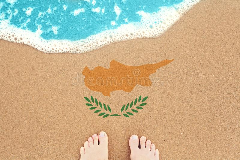Feet on the sunny sandy beach with flag Cyprus. View from top on surf.  royalty free stock photos