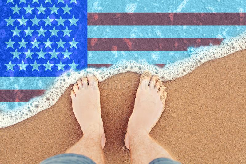 Feet on the sunny sandy beach with flag USA. Top View on sea surf.  royalty free stock image