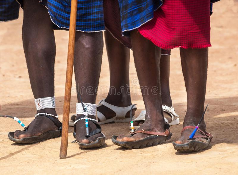 Feet three men of the Masai Mara tribe & x28;indigenous tribe of Kenya& x29;. Recycled rubber tires become Masai`s sandals royalty free stock image
