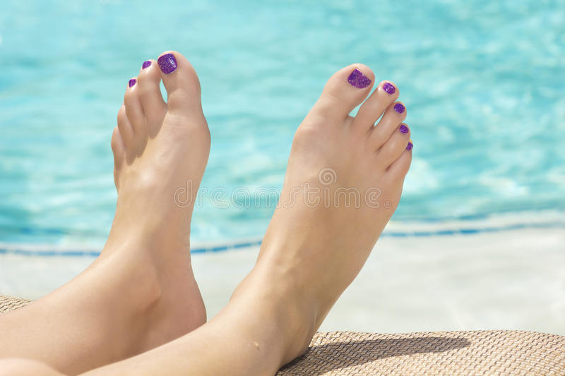 Feet and toes by the Swimming Pool. Beautiful female feet relaxing by the swimming pool. Great pedicure photo stock photography