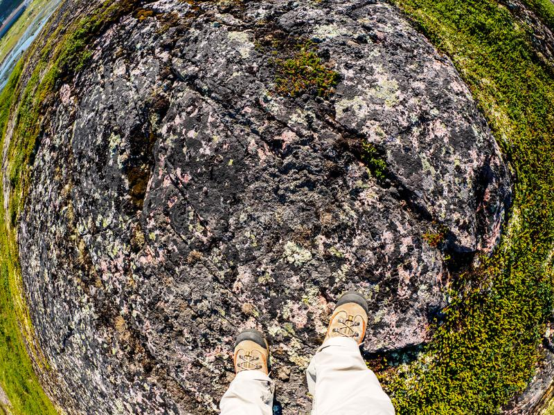 Feet of tourist in sport hiking shoes walking on the tundra. Concept for travelling and adventure. Fish eye lens image stock photos