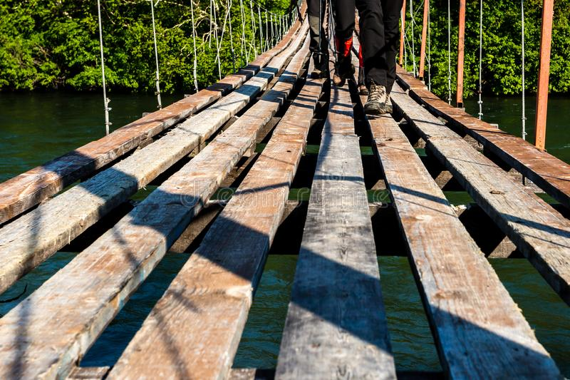 Feet of tourists in sport hiking shoes walking on the wooden suspension bridge. Concept for travelling and adventure. Feet of tourists in sport hiking shoes stock photos