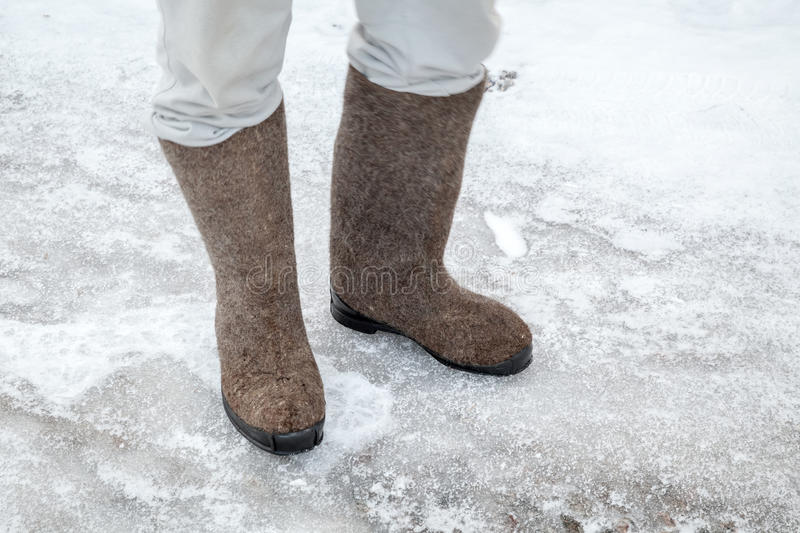 Feet with traditional Russian felt boots on winter road royalty free stock photo