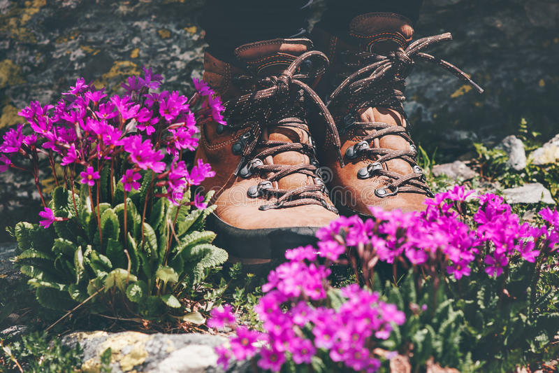 Feet trekking boots at pink flowers valley stock photo