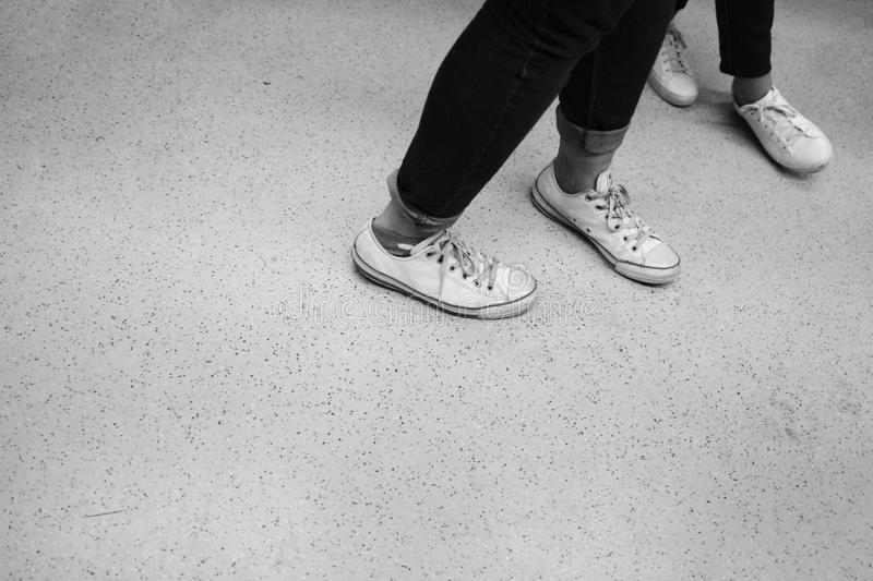 Feet of two dancers in white shoes royalty free stock photography