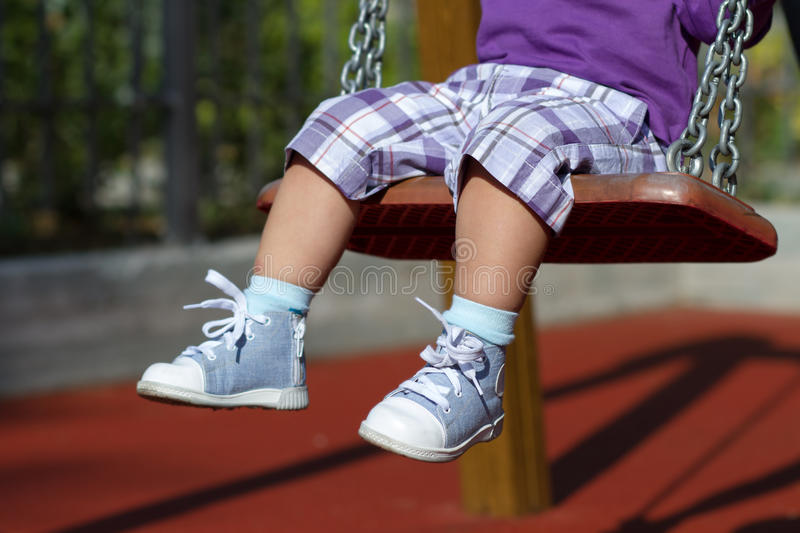 Feet of unrecognizable baby swinging on playground royalty free stock photo
