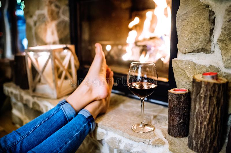Feet of unrecognizable woman in front of the fireplace. royalty free stock photography