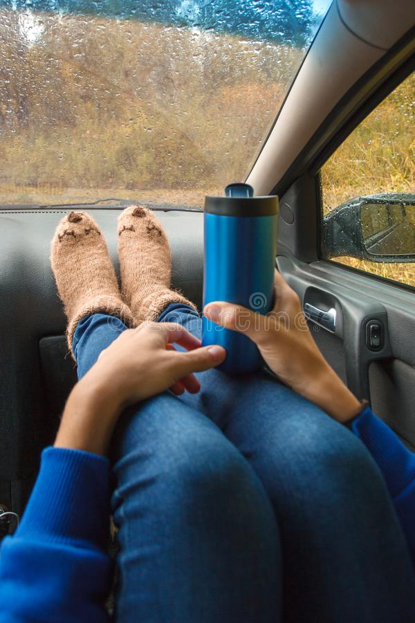 Feet in warm cute socks on car dashboard. Travel, road trip and autumn fall concept. Focus on thermos bottle cup with hot drink. In female hands royalty free stock photos