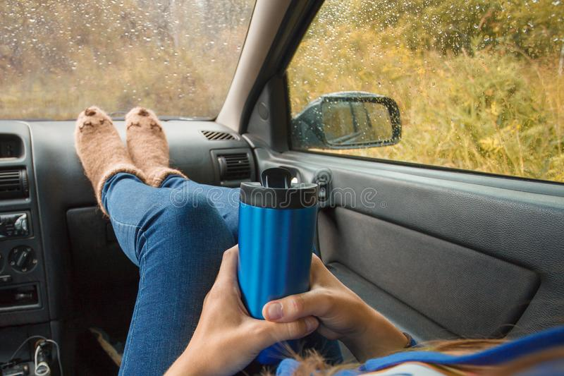 Feet in warm cute socks on car dashboard. Travel, road trip and autumn fall concept. Focus on thermos bottle cup with hot drink. In female hands. Autumn car royalty free stock images