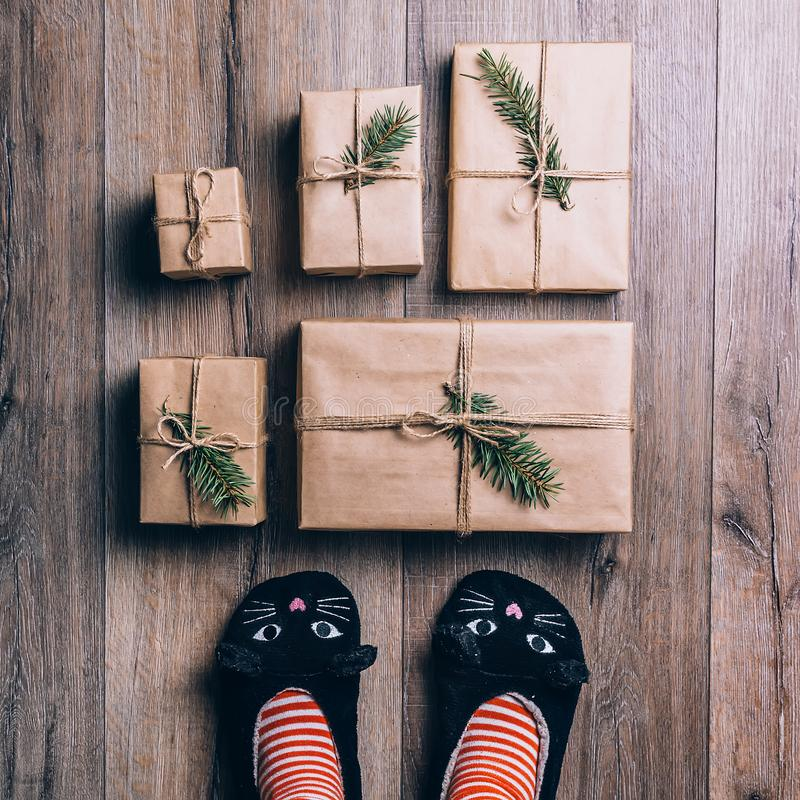 Feet with warm winter socks and cat slippers standing in front of Christmas gifts. top view. royalty free stock photography